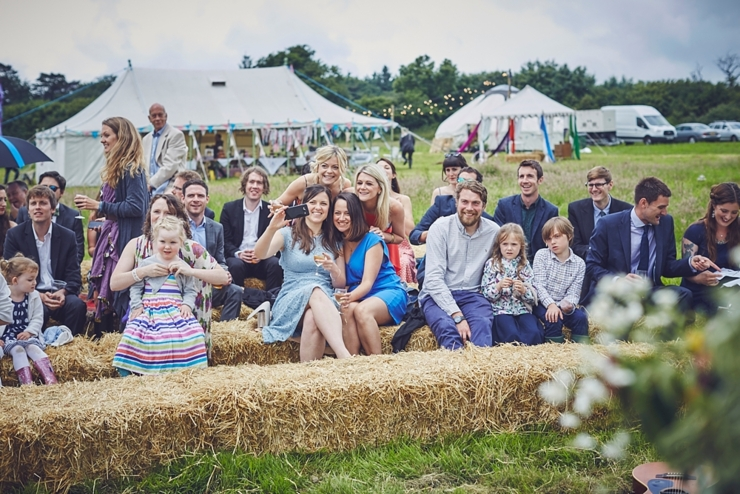 guests on hay bales at outdoor wedding blessing in Dorset