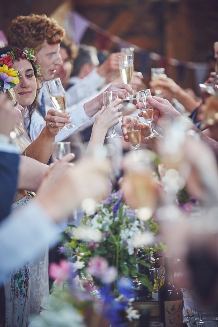 guests clinking glasses after the speeches at a boho wedding in Dorset uk