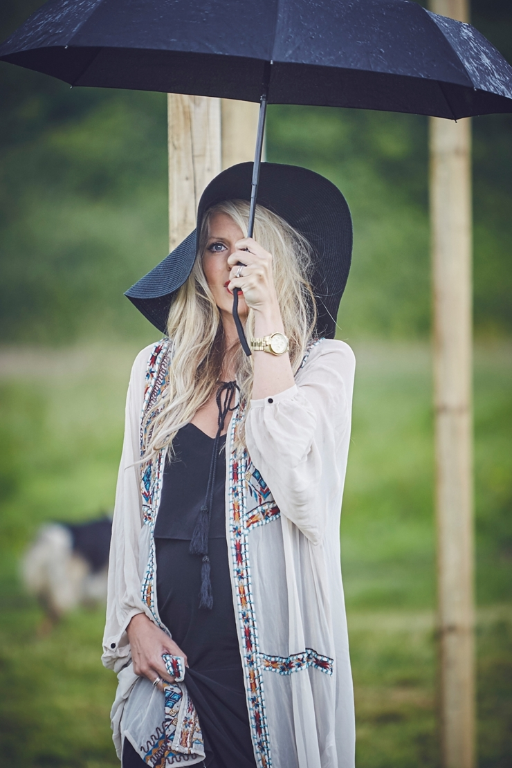 cool female guest with 70's hat obscured by umbrella at a rainy boho wedding in Dorset