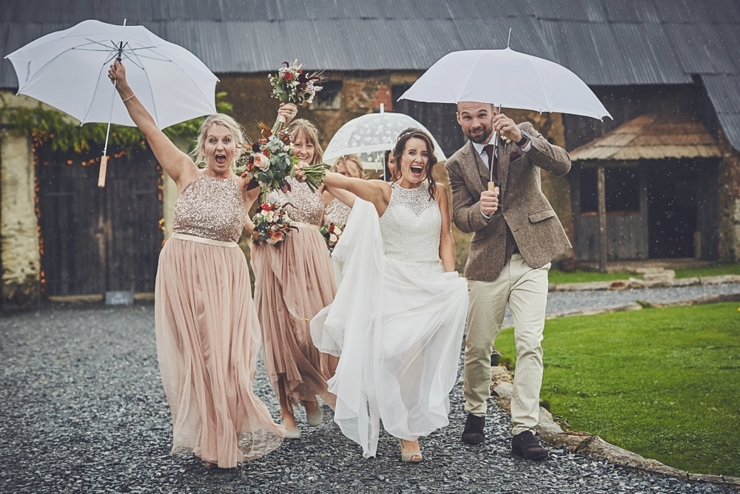 wedding party running laughing with umbrellas at a rainy wedding in Devon