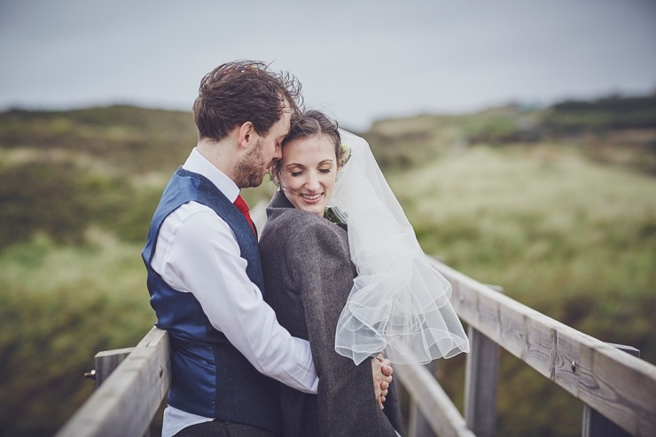 couple keep each other warm during portraits at a wedding in Devon barn at South Milton