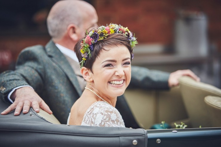 bride Megan smiling in vintage wedding car just before her hand tying ceremony at West Town Farm in Exeter