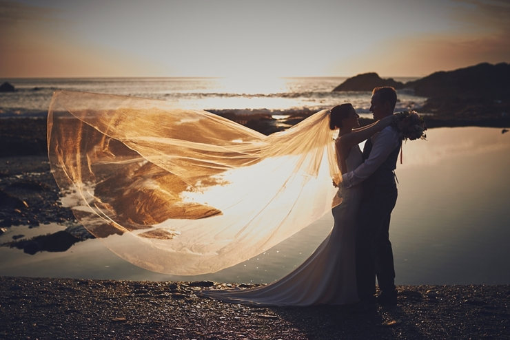 portraits at Tunnels Beaches wedding at sunset with veil blowing