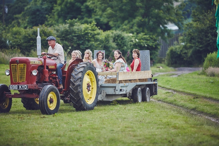 Bridal party arrival to outdoor ceremony on a tractor.jpg