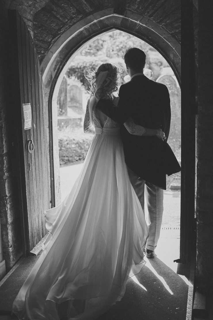 bride and groom in entrance of church in Devon