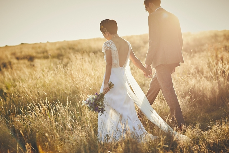 bride and groom walk through wheat field in the golden hour sunset