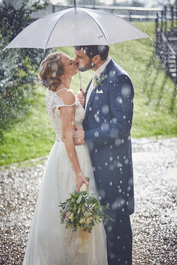bride and groom kissing under an umbrella in the rain at a Somerset wedding
