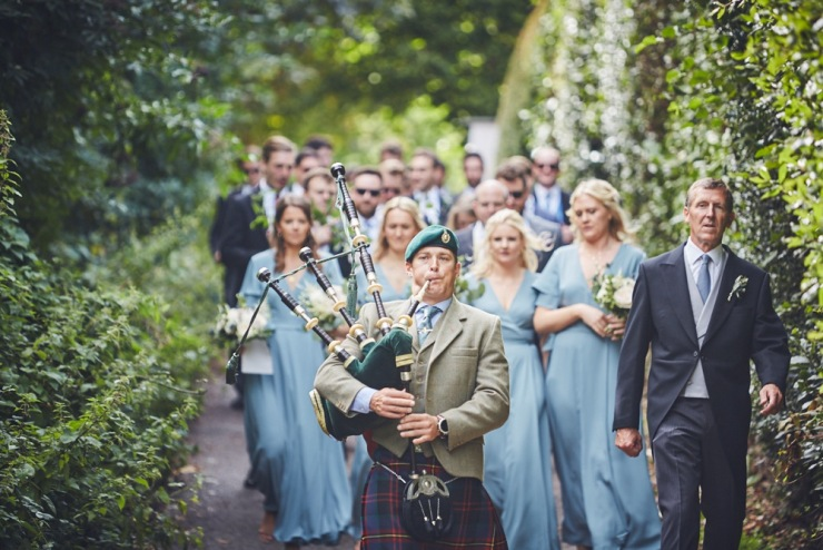 candid wedding photography of bag pipe player at devon wedding