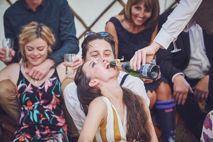 guest having fizz poured sown her throat at a boho wedding in Dorset