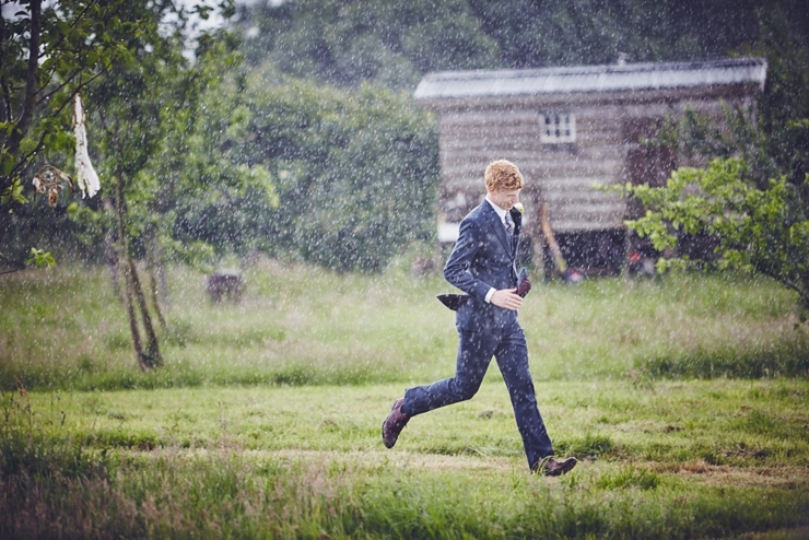 Groom running in the rain at a boho outdoor wedding in Dorset